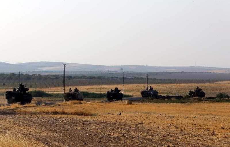 Turkish armoured personnel carriers drive towards the border in Karkamis on the Turkish-Syrian border in the southeastern Gaziantep province, Turkey, August 27,