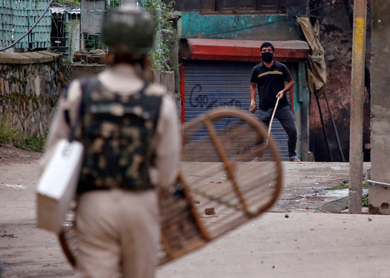 A protester prepares to throw a stone towards an Indian policeman during a protest in Srinagar against the recent killings in Kashmir