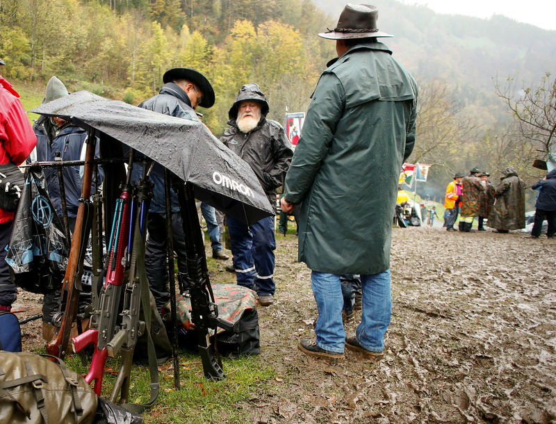 Participants use an umbrella to protect their infantry and assault rifles against rain during the traditional 'Ruetlischiessen' (Ruetli shooting) competition at the Ruetli meadow in central Switzerland