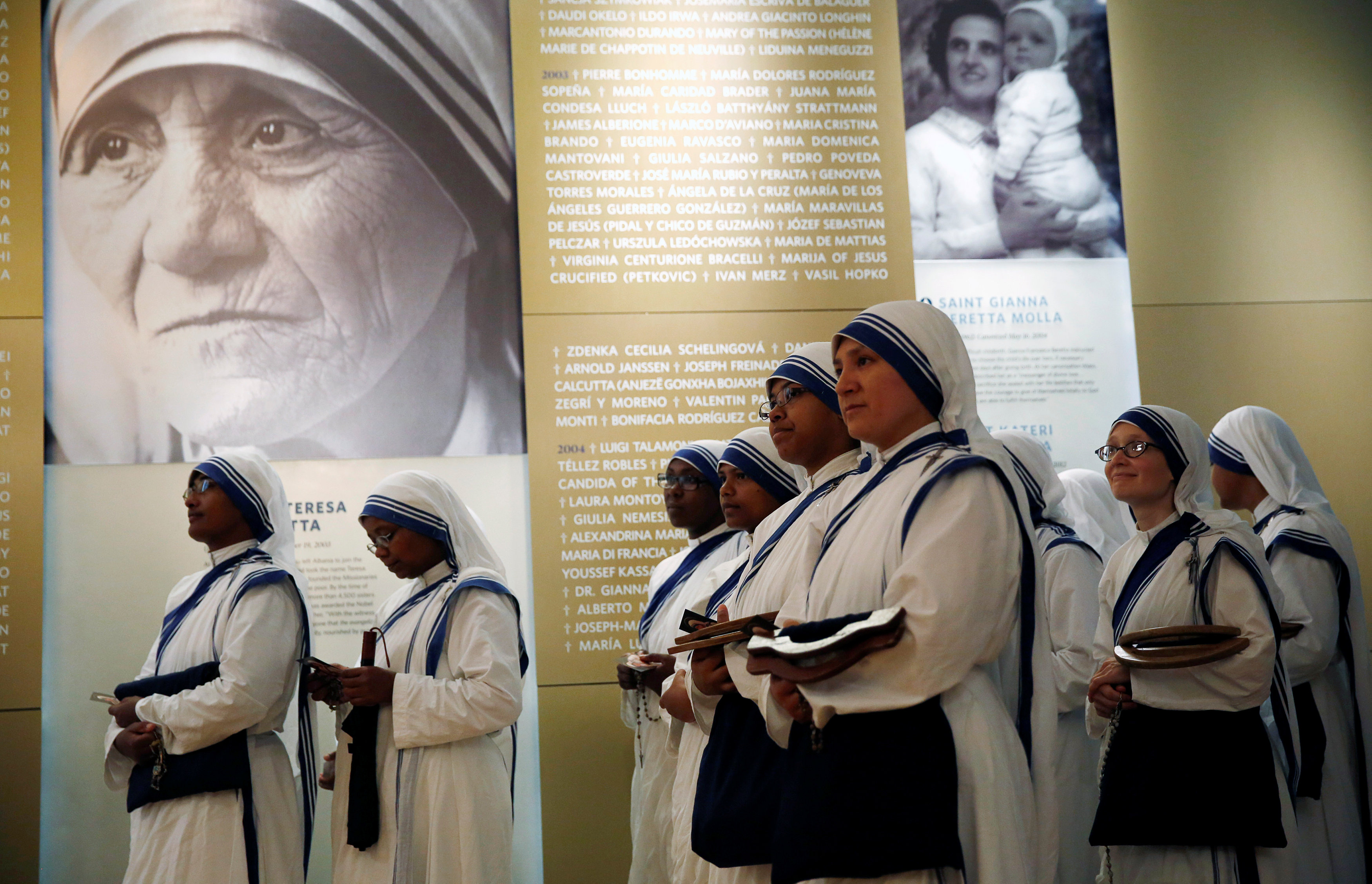 Members of Mother Teresa's order, the Missionaries of Charity, stand under a photograph before the unveiling of an official canonization portrait at the John Paul II National Shrine in Washington