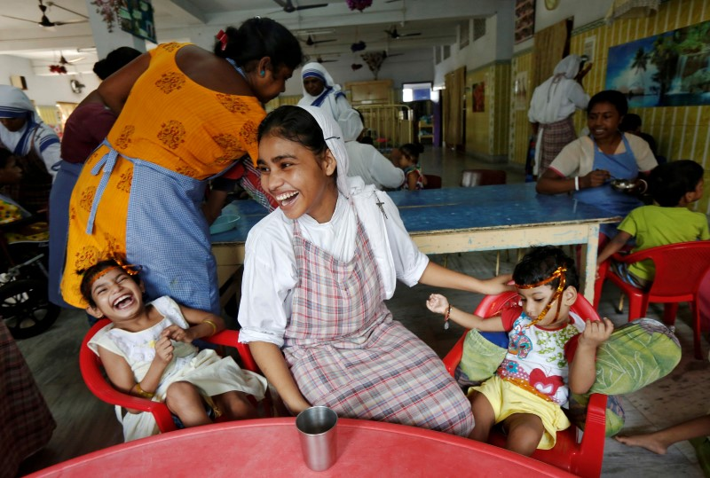 A nun belonging to the global Missionaries of Charity reacts as she interacts with children at the Nirmala Shishu Bhavan in Inda