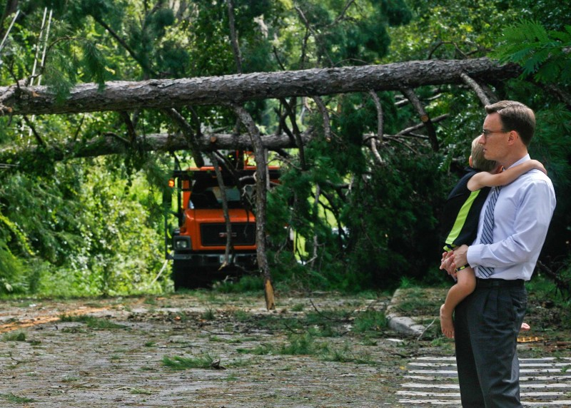 Robert Long and his son J.D. watch workers removing downed trees during cleanup operations in the aftermath of Hurricane Hermine in Tallahassee