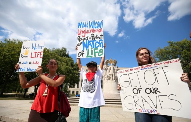 Protesters hold signs outside the U.S. District Court in Washington, where a hearing was being held to decide whether to halt construction of an oil pipeline in parts of North Dakota where a Native American tribe says it has ancient burial and prayer sites,