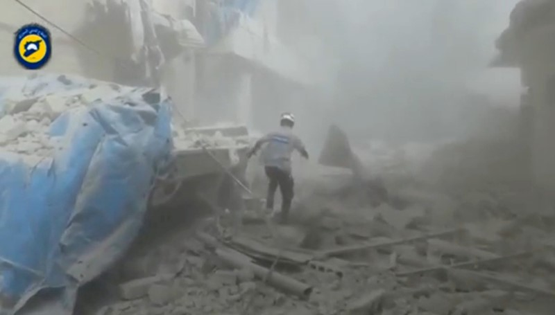 A still image taken on September 7, 2016 from a video posted on social media said to be shot in Aleppo's Al Sukari on September 6, 2016, shows a civil defense member making his way through debris, after a suspected chlorine gas attack,