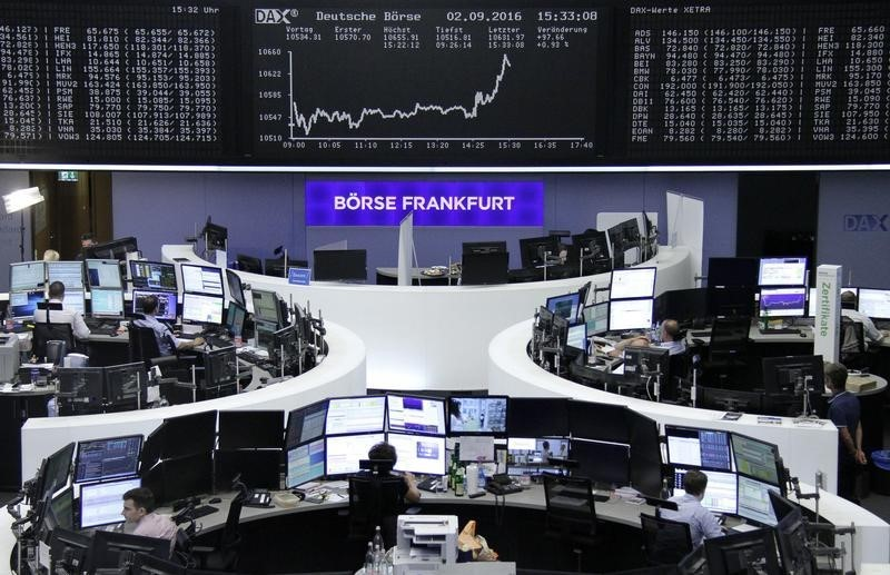 Traders work at their desks in front of the German share price index, DAX board, at the stock exchange in Frankfurt, Germany,
