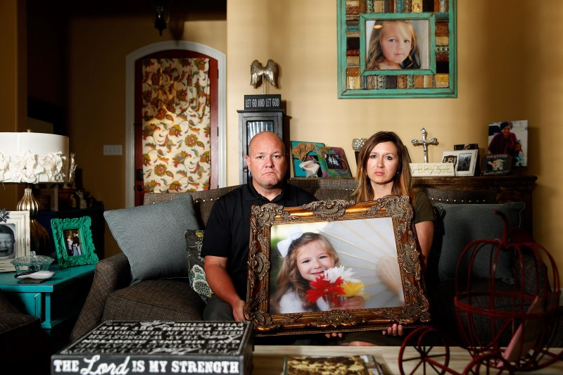 Kelly and Ryan Breaux sit holding a portrait of their deceased daughter Emma Breaux in their home in Breaux Bridge, Louisiana, on June 16, 2016. The husband and wife lost twins, Emma and Talon, to different superbugs that they contracted while in the neonatal unit at Lafayette General Hospital.