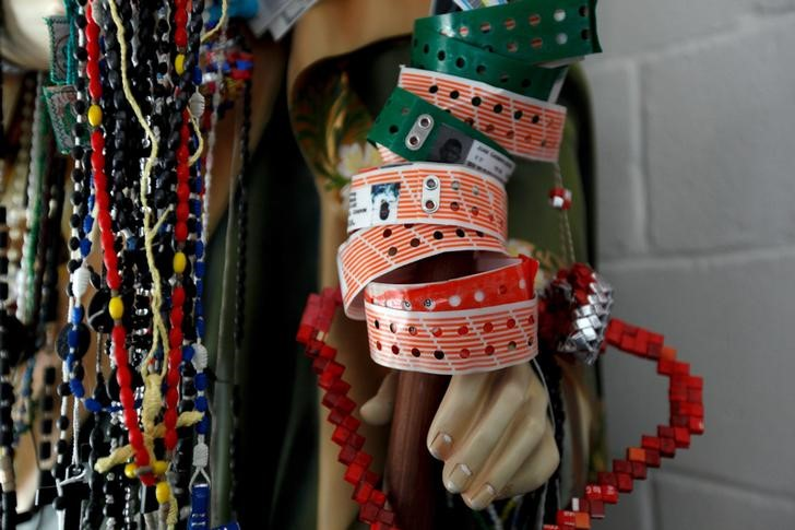 U.S. migrant detention center bracelets and rosaries hang from a religious statue at a migrant shelter in Ciudad Juarez, Mexico,