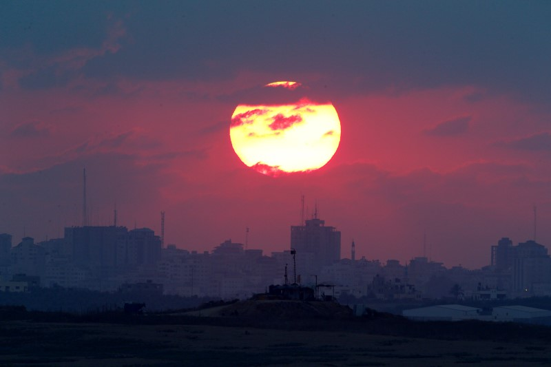 The sun sets over the Gaza Strip, as seen from the Israeli side