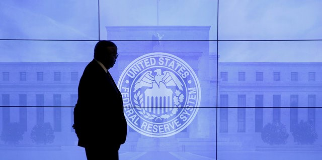A security guard walks in front of an image of the Federal Reserve following the two-day Federal Open Market Committee (FOMC) policy meeting in Washington, DC
