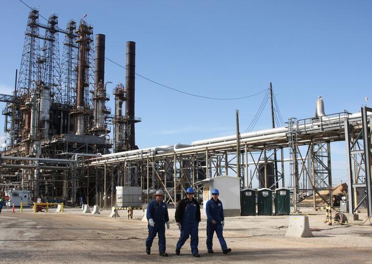 Refinery workers walk inside the LyondellBasell oil refinery in Houston, Texas