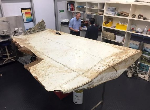 Australian and Malaysian officials examine aircraft debris at the Australian Transport Safety Bureau headquarters in Canberra, Australia, after it was found on Pemba Island, located near Tanzania, in late June.