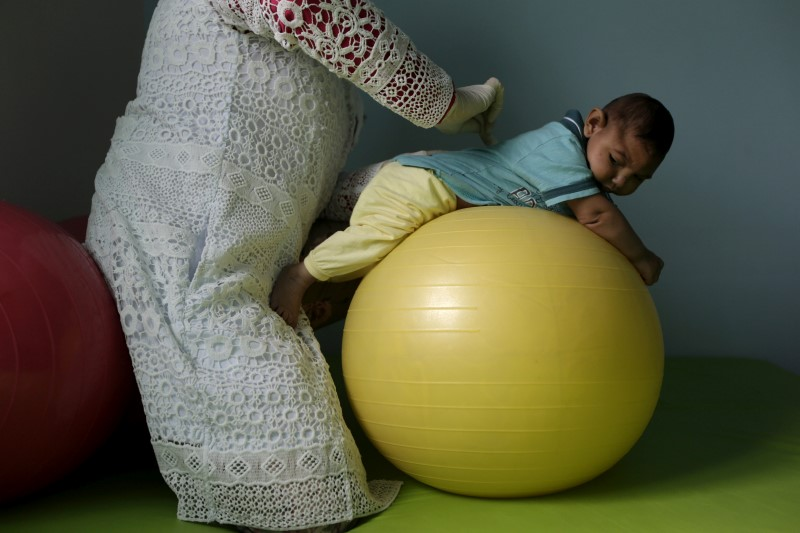 Physiotherapist Leal does exercises with Lucas, 4-months old, who is Miriam Araujo's second child and born with microcephaly in Pedro I hospital in Campina