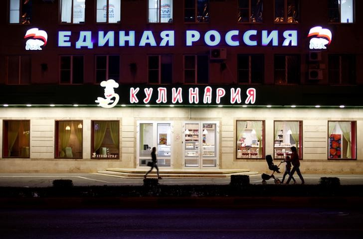 """People walk past a sign reading """"United Russia"""" on a building in central Stavropol, Russia,"""