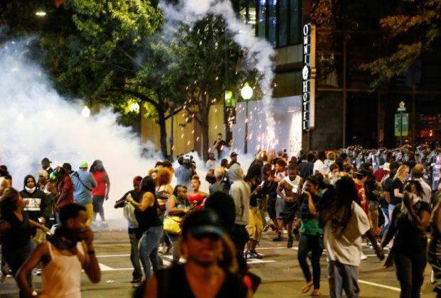 People running from flash bang grenades at Charlotte riot