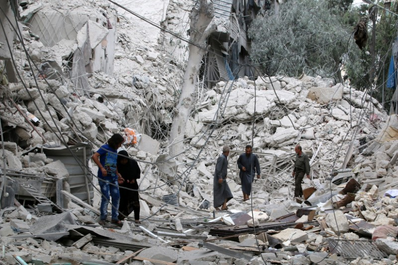 People inspect a damaged site after airstrikes on the rebel held Tariq al-Bab neighbourhood of Aleppo