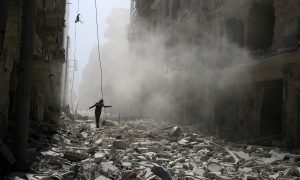 A man walks on the rubble of damaged buildings after an airstrike on the rebel held al-Qaterji neighbourhood of Aleppo, Syria September 25, 2016.