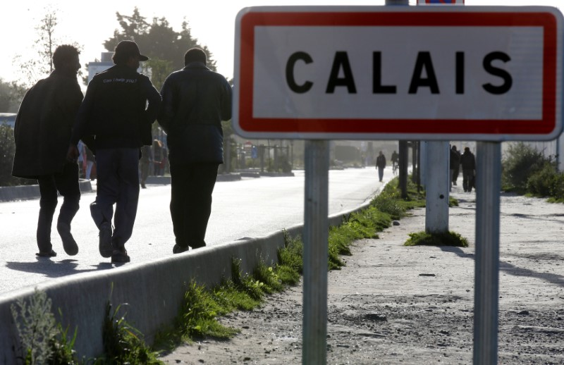 "Migrants pass by a road sign as they leave the northern area of the camp called the ""Jungle"" in Calais, France,"