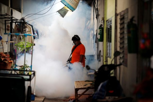 A city worker fumigates the area to control the spread of mosquitoes at a university in Bangkok, Thailand,