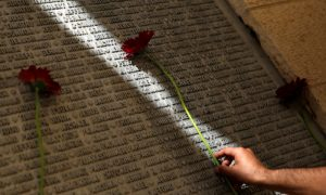 A man lays a flower on a monument engraved with names of victims of the September 11th attacks, during a memorial event marking the 15th anniversary