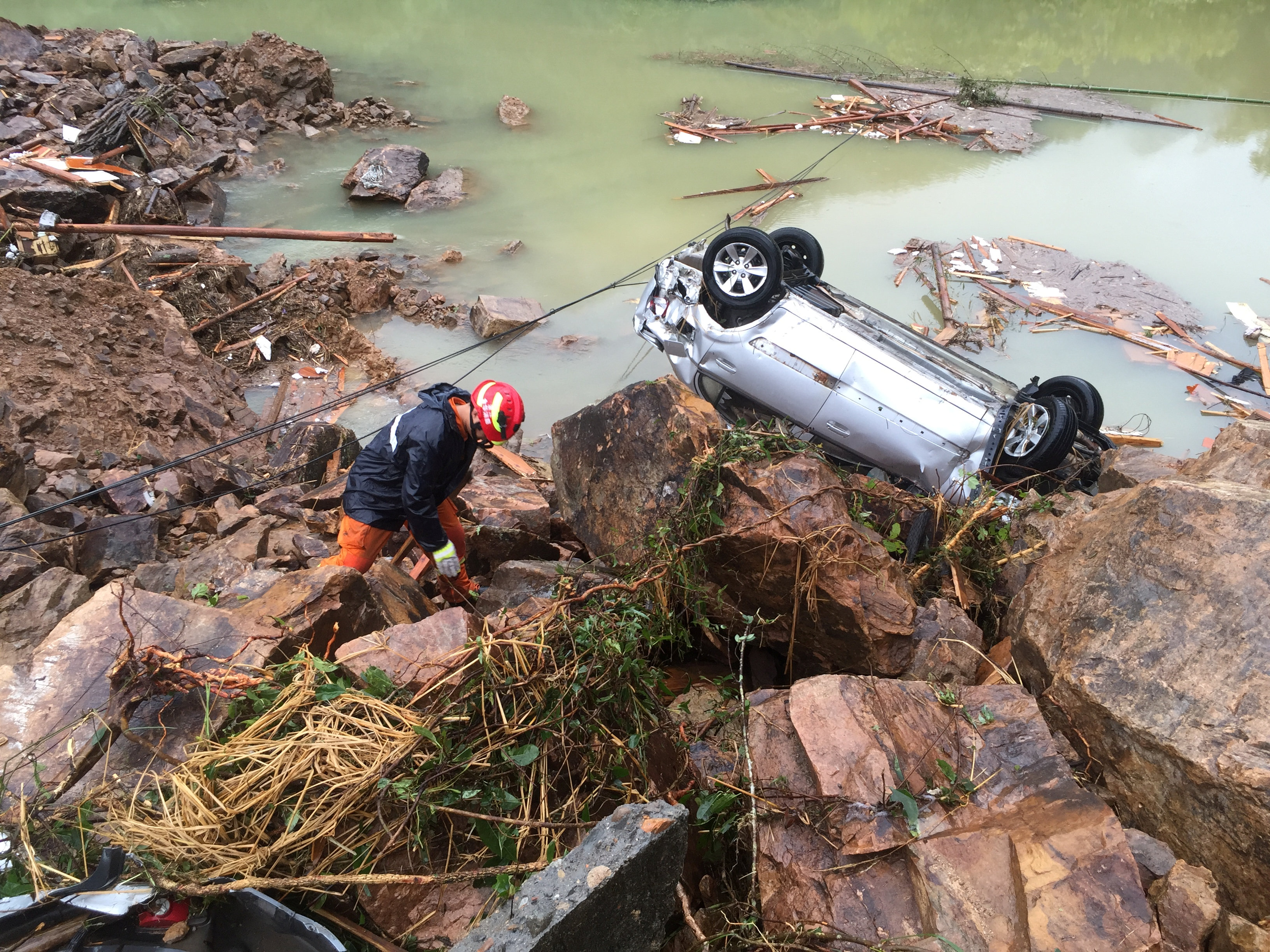 A rescue worker is seen next to an overturned car at the site of a landslide caused by heavy rains brought by Typhoon Megi, in Sucun Village, Lishui