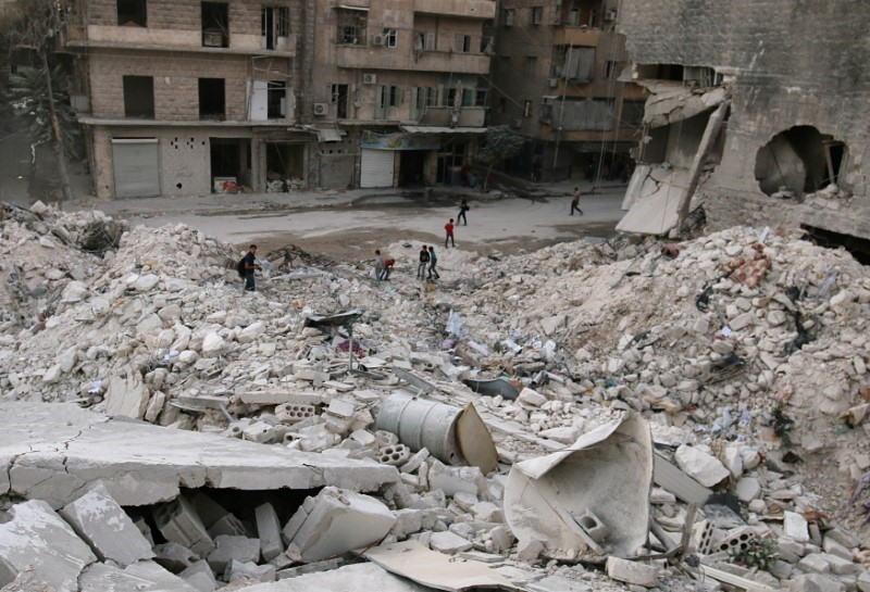 People walk on the rubble of damaged buildings in the rebel held area of al-Kalaseh neighbourhood of Aleppo,