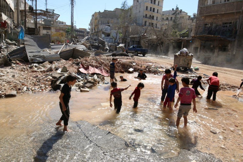 Children play with water from a burst water pipe at a site hit yesterday by an air strike in Aleppo's rebel-controlled al-Mashad neighbourhood, Syria,