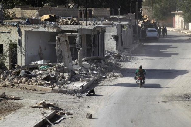 A rebel fighter rides past damaged buildings in al-Rai town, northern Aleppo countryside,