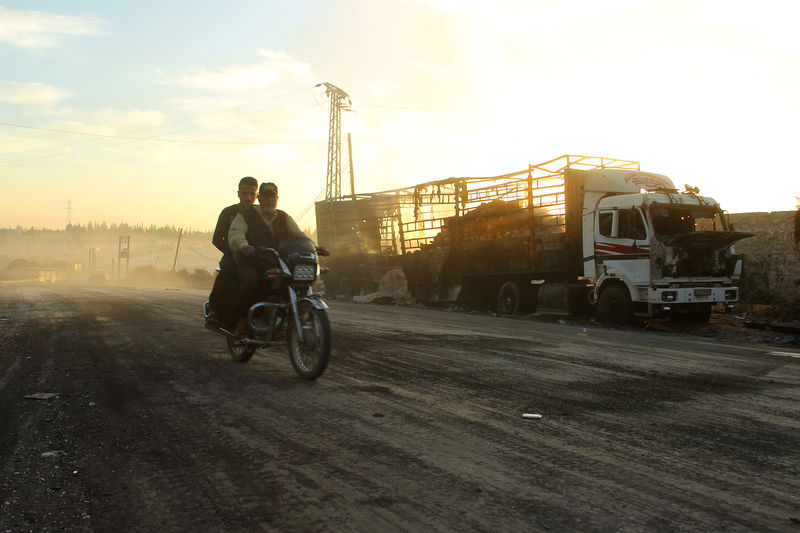 Men drive a motorcycle near a damaged aid truck after an airstrike on the rebel held Urm al-Kubra town, western Aleppo city, Syria September 20, 2016.