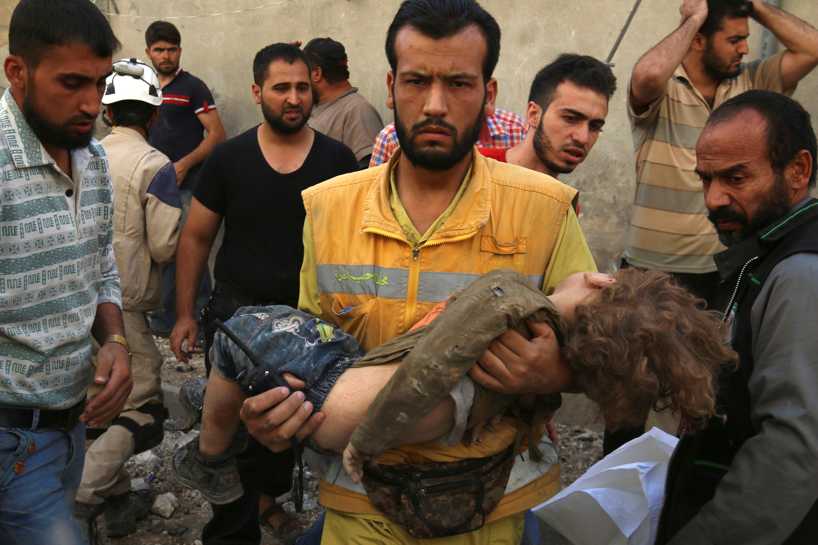 A medic holds a dead child after airstrikes in the rebel held Karam Houmid neighbourhood in Aleppo