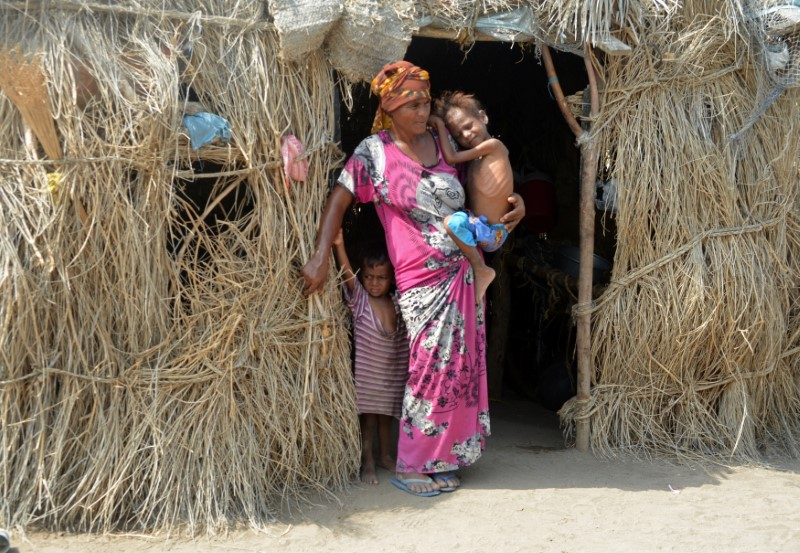 A woman holds her child at the door of her hut in al-Tuhaita district of the Red Sea province of Hodaida, Yemen