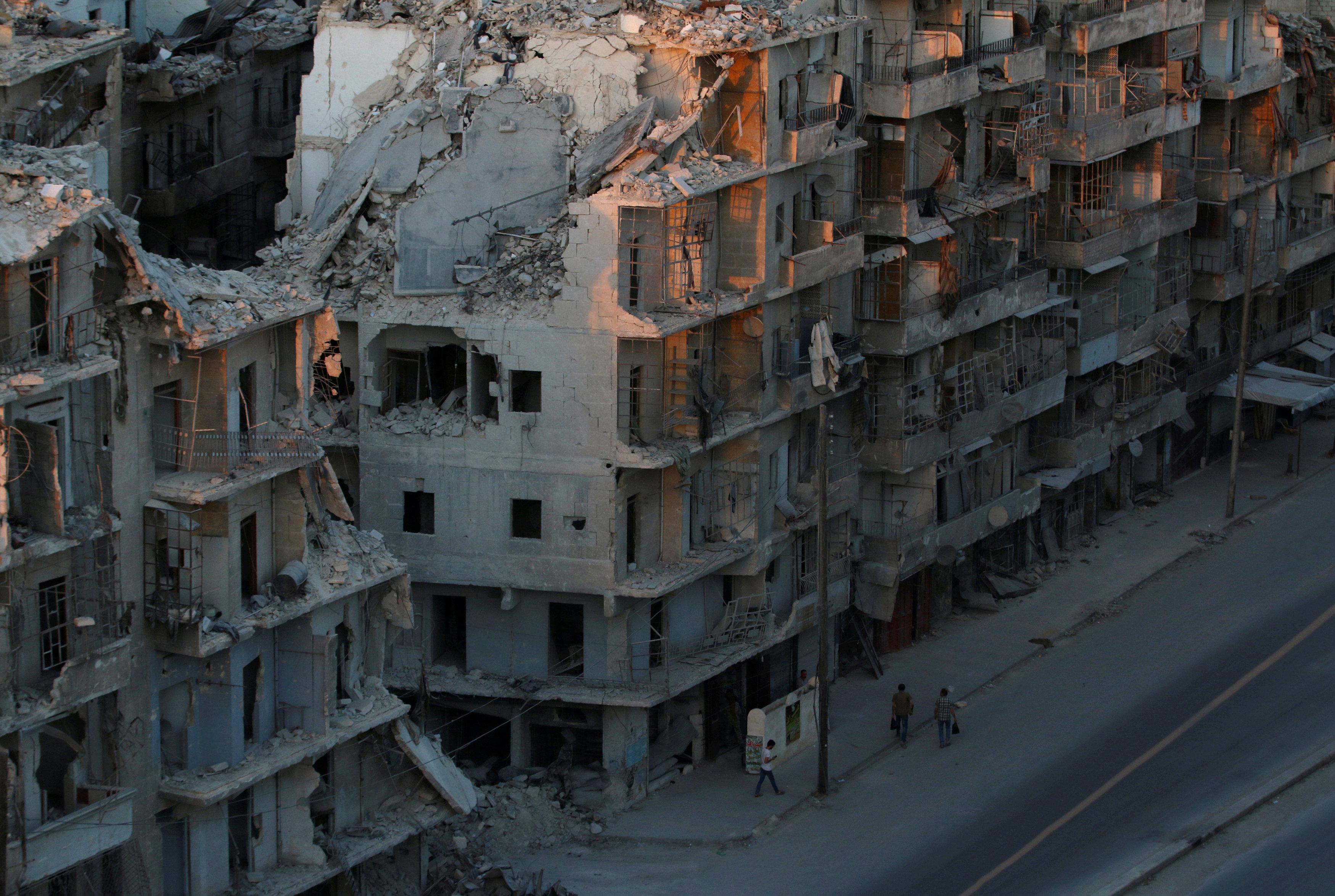 People walk past damaged buildings in the rebel-held Tariq al-Bab neighbourhood of Aleppo, Syria,