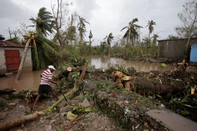 A man cuts branches off fallen trees in a flooded area by a river after Hurricane Matthew in Les Cayes, Haiti,