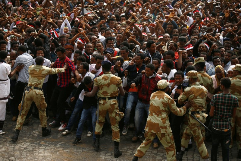 Demonstrators chant slogans while flashing the Oromo protest gesture during Irreecha, the thanksgiving festival of the Oromo people, in Bishoftu town, Oromiya region, Ethiopia, i