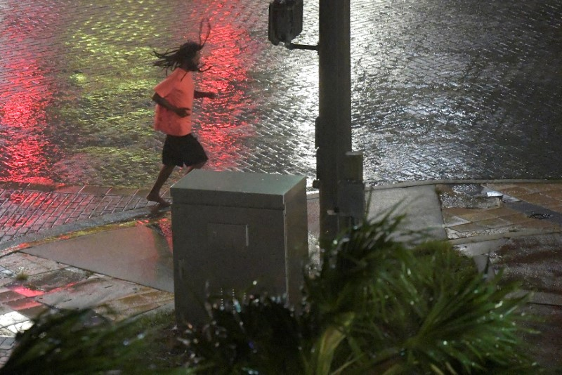A pedestrian runs across a street as the eye of Hurricane Matthew approaches Daytona Beach, Florida,