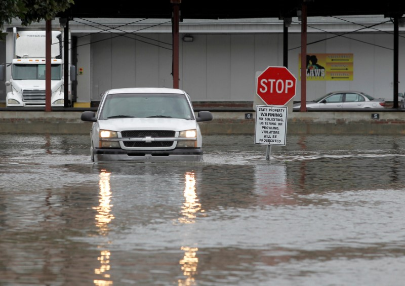 A truck passes through flooded water at a business after Hurricane Matthew passed through in Savannah, Georgia