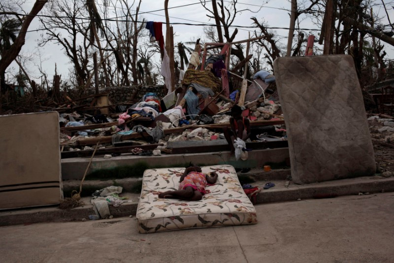 Two girls play amid the rubble after Hurricane Matthew in a street of Port-a-Piment, Haiti,