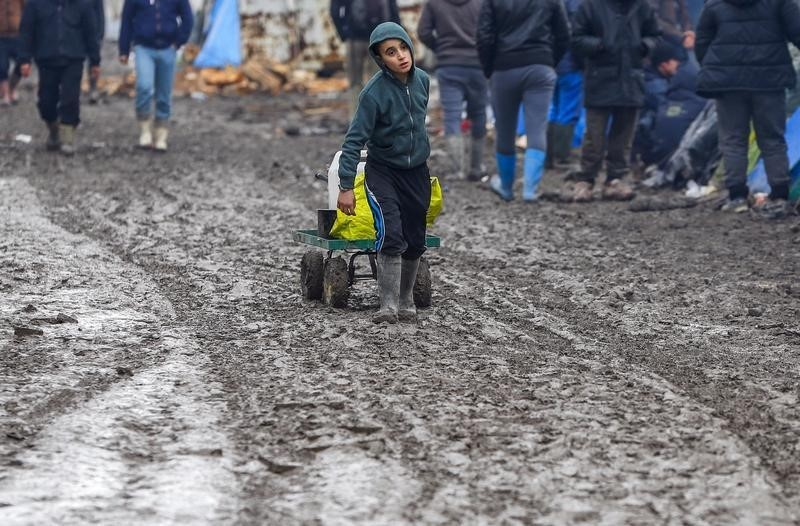 A young migrant pulls a trolley in a muddy field at a camp of makeshift shelters for migrants and asylum-seekers from Iraq, Kurdistan, Iran and Syria, called the Grande Synthe jungle, near Calais, France,