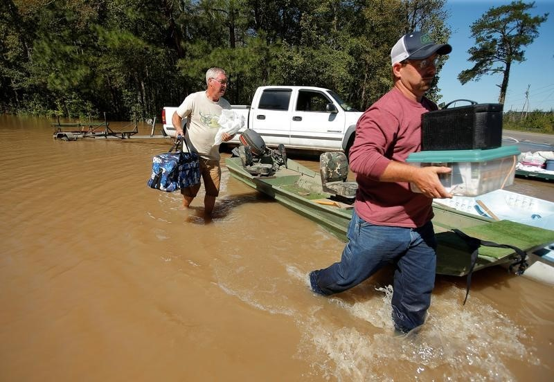 Men carry belongings from a neighbours home as flood waters rise after Hurricane Matthew in Lumberton, North Carolina,