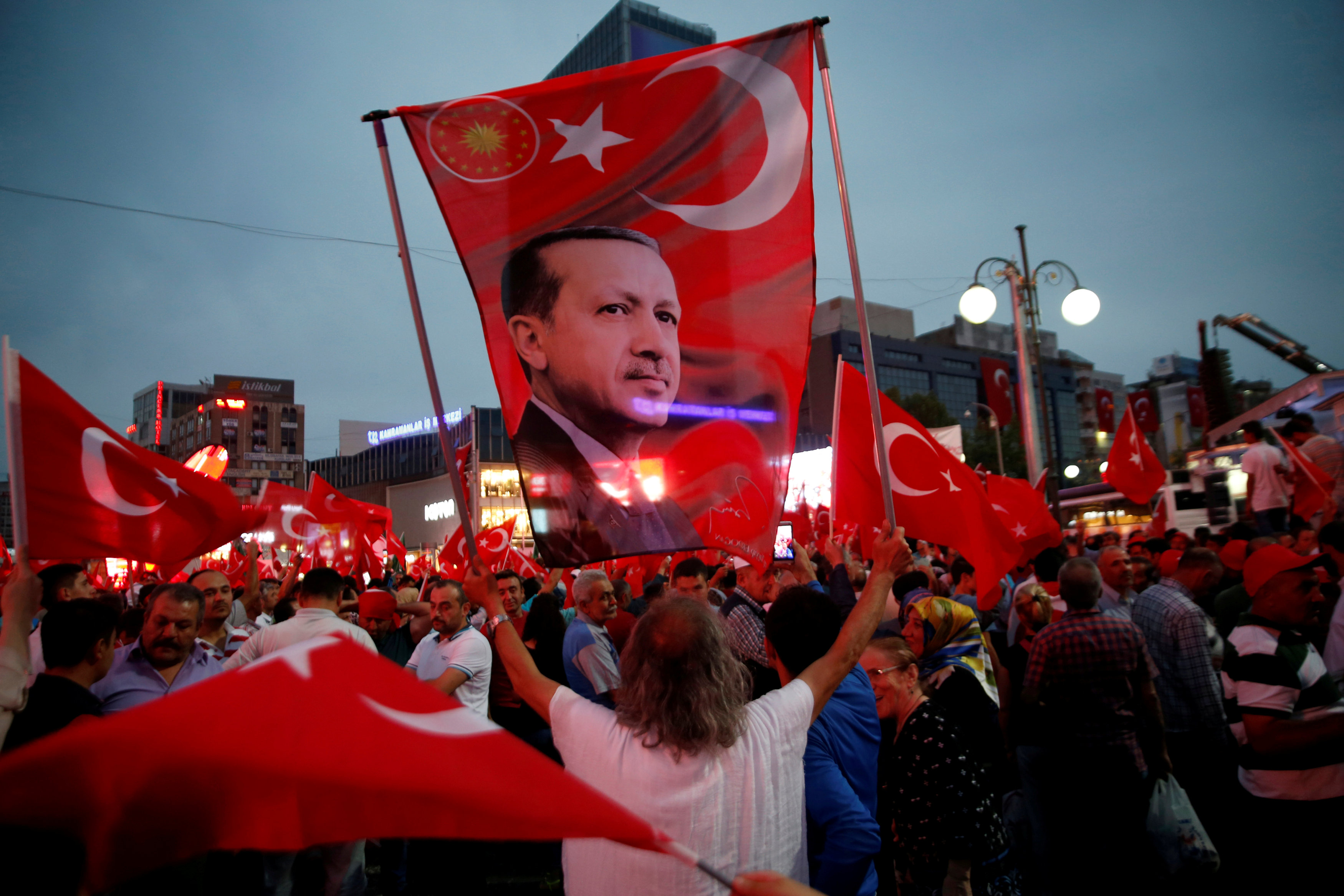 A supporter holds a flag depicting Turkish President Tayyip Erdogan during a pro-government demonstration in Ankara, Turkey,