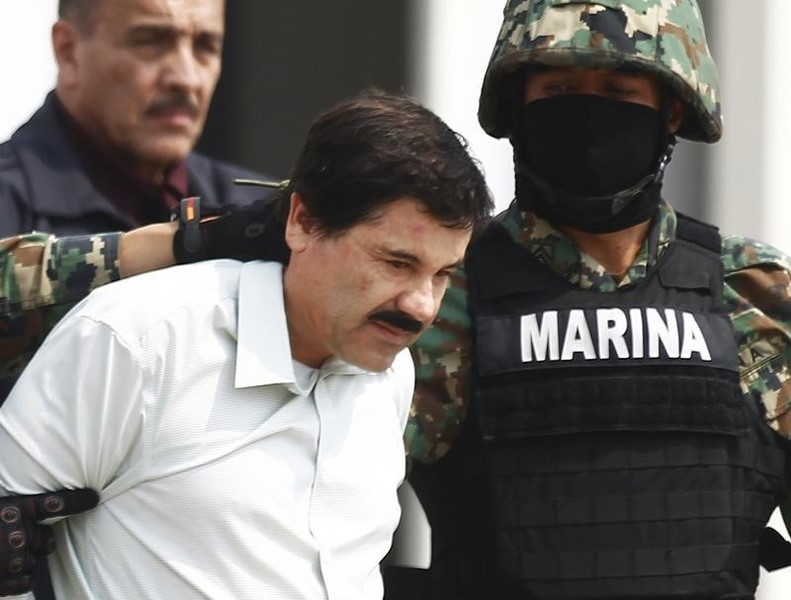 """Joaquin """"Shorty"""" Guzman (C) is escorted by soldiers during a presentation at the Navy's airstrip in Mexico City February 22, 2014."""