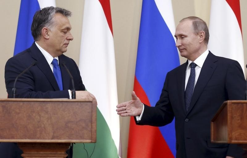Russian President Vladimir Putin (R) and Hungarian Prime Minister Viktor Orban shake hands during a joint news conference following their talks at the Novo-Ogaryovo state residence outside Moscow, Russia,