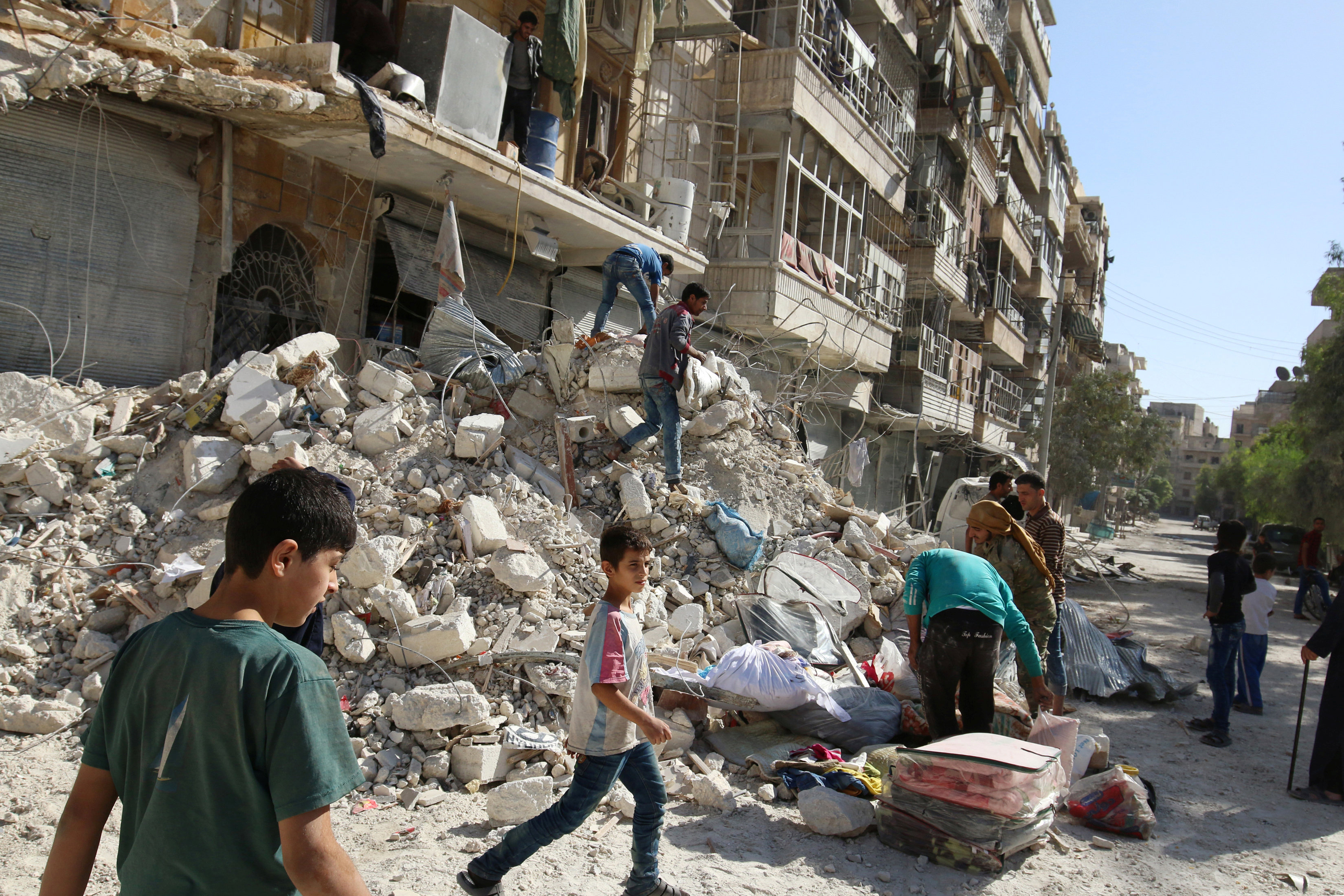 People remove belongings from a damaged site after an air strike Sunday in the rebel-held besieged al-Qaterji neighbourhood of Aleppo, Syria
