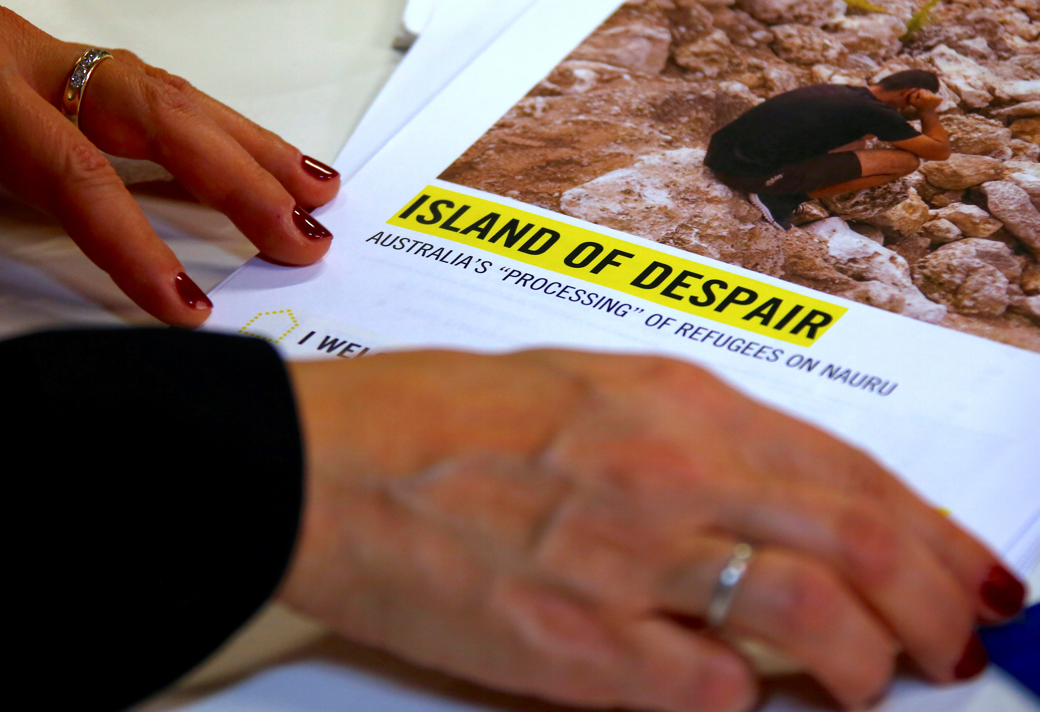"Anna Neistat, Senior Director for Research with Amnesty International, talks to journalists as she holds a copy of a report she co-authored titled 'Island of Despair - Australia's ""Processing"" of Refugees on Nauru' in Sydney, Australia"