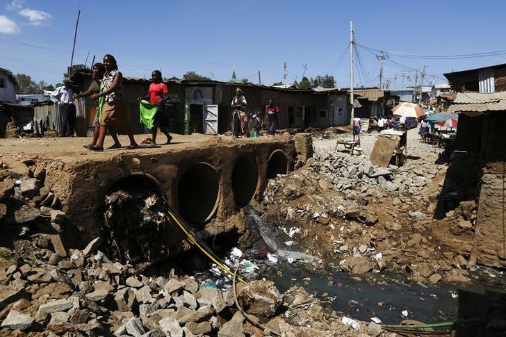 People walk near open sewers in the Kibera slum of Kenya's capital Nairob