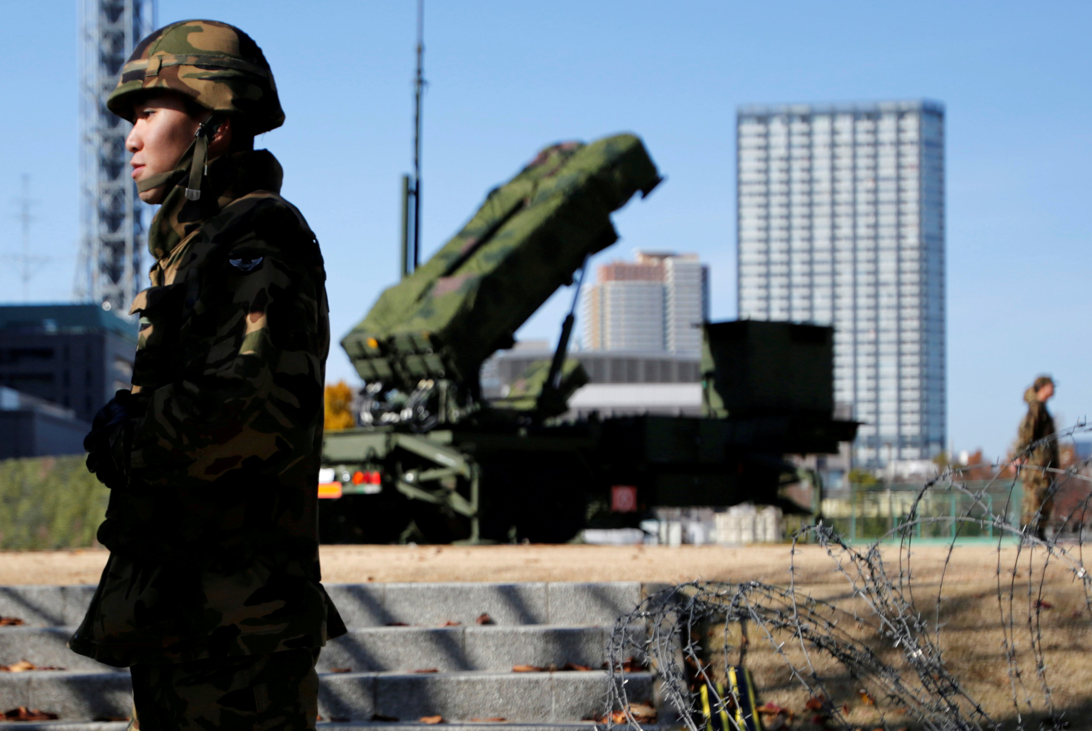 Members of the Japan Self-Defence Forces stand guard near Patriot Advanced Capability-3 (PAC-3) land-to-air missiles, deployed at the Defense Ministry in Tokyo, Japan