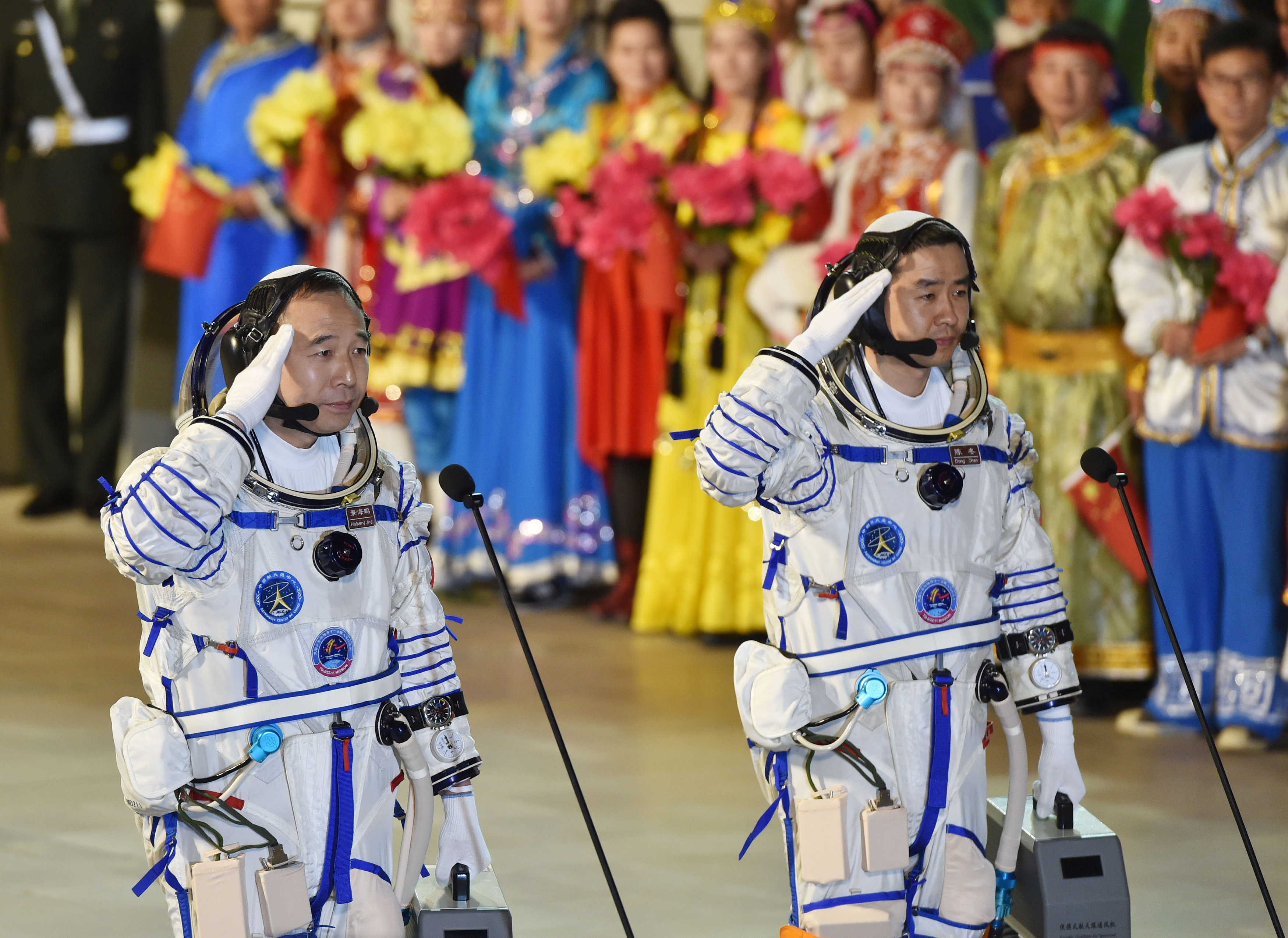 Chinese astronauts Jing Haipeng (L), Chen Dong salute before the launch of Shenzhou-11 manned spacecraft, in Jiuquan, China,