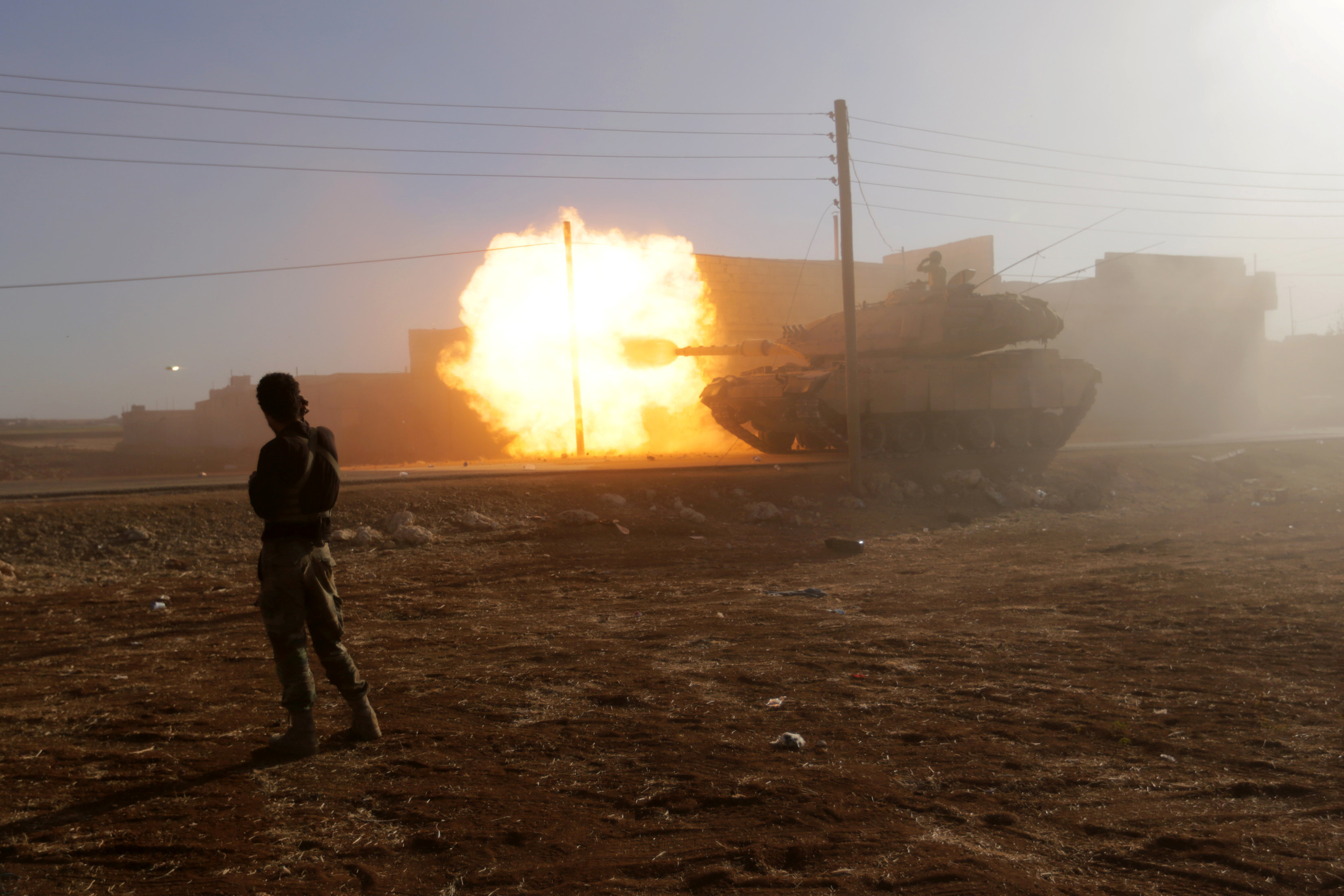 A rebel fighter stands near a Turkish tank as it fires towards Guzhe village, northern Aleppo countryside, Syria