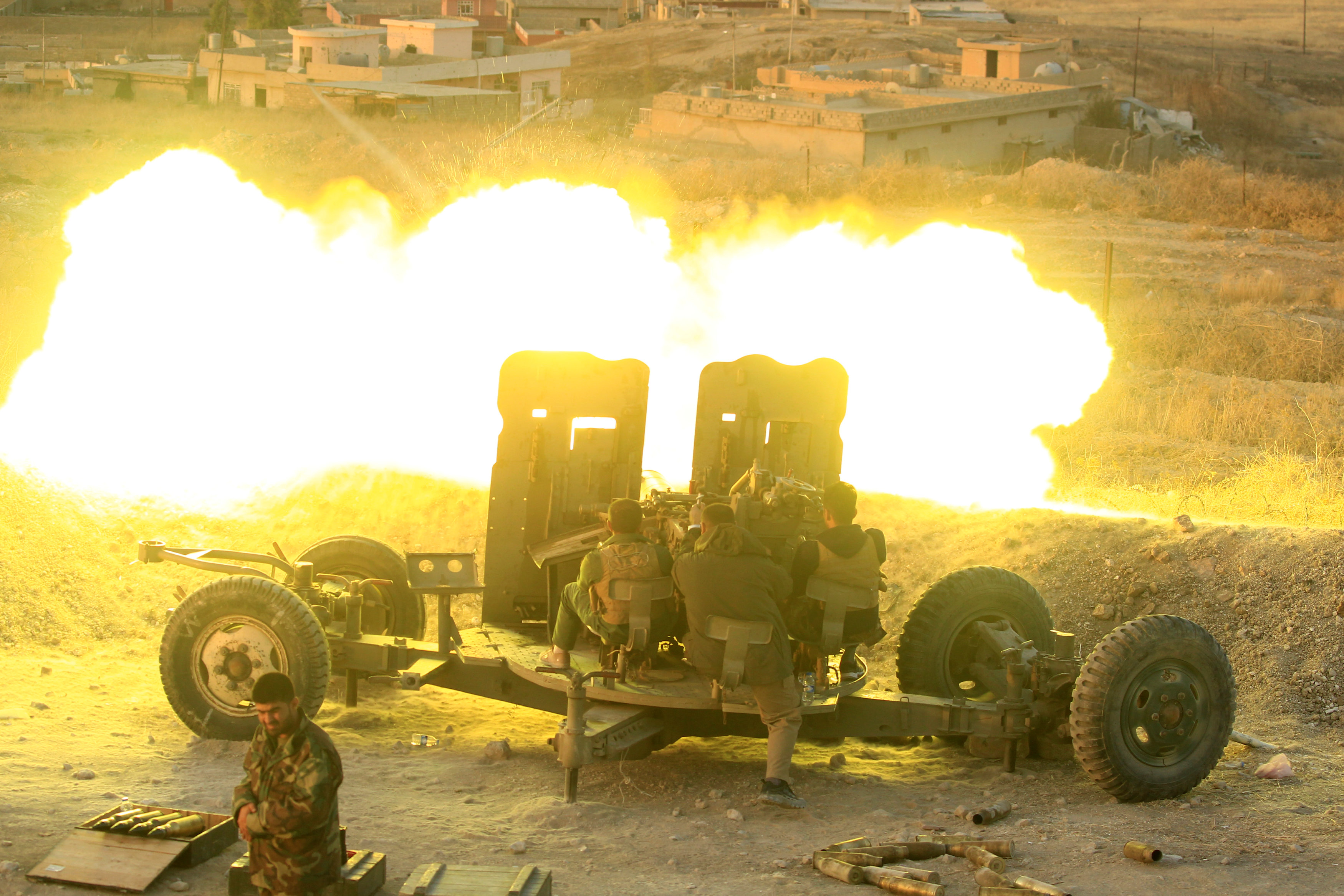 Peshmerga forces fire an anti-aircraft gun towards Islamic state militants positions in the town of Naweran near Mosul, Iraq