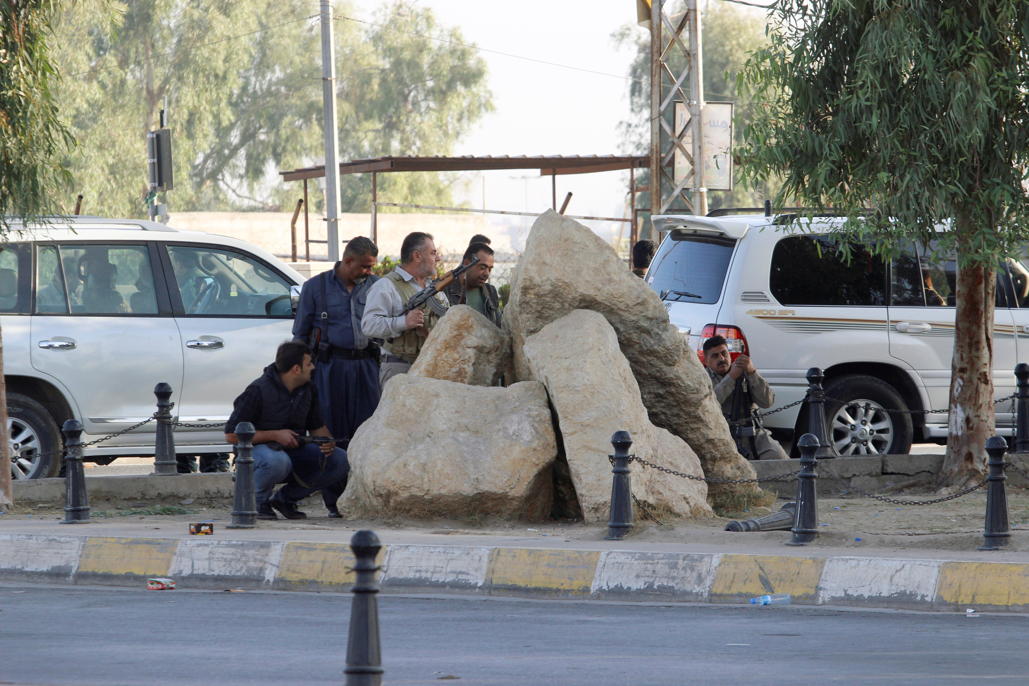 Peshmerga forces stand behind rocks at a site of an attack by Islamic State militants in Kirkuk, Iraq,