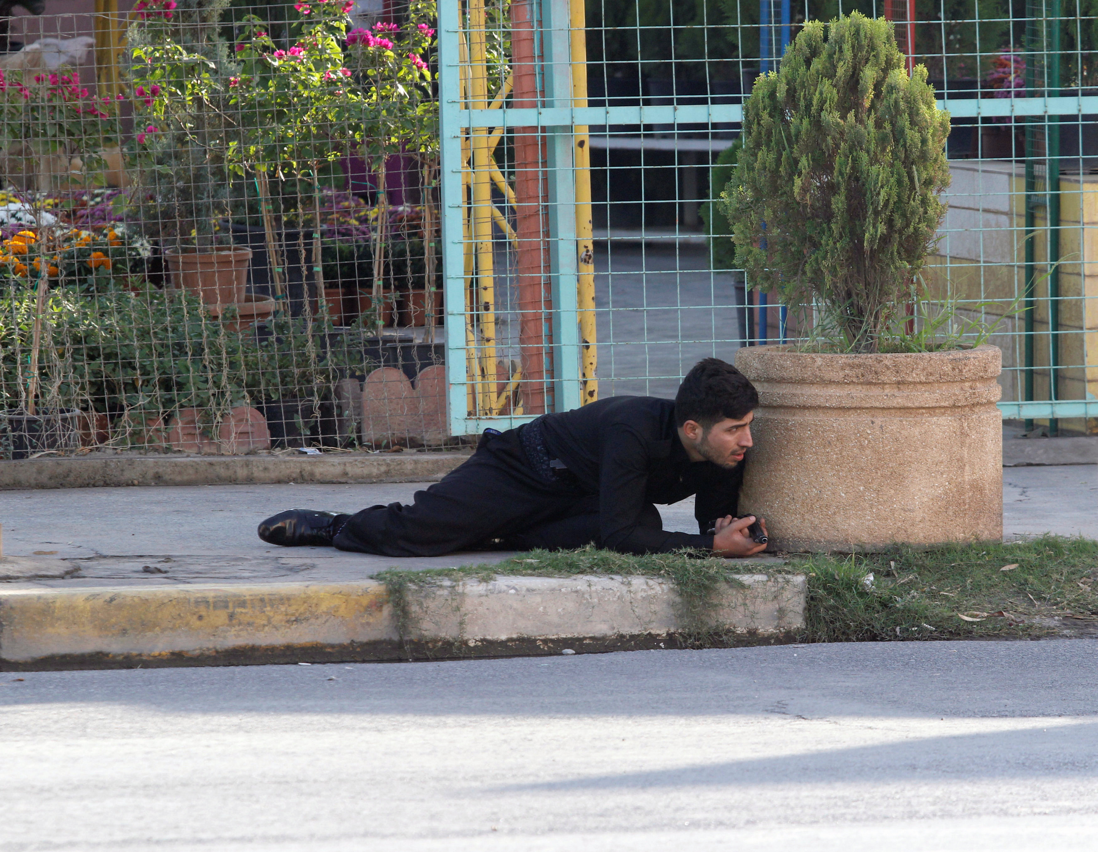 A Kurdish security personnel takes cover at a site of an attack by Islamic State militants in Kirkuk, Iraq,